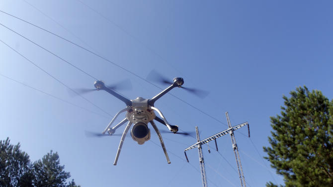 This June 22, 2015 photo shows a drone lifting off at a Georgia Power training complex during power line inspection demonstration in Lithonia, Ga. Power companies across the United States are testing whether drones as small as 10 pounds can spot trouble on transmission lines or inspect equipment deep inside hard-to-reach power plant boilers. (AP Photo/John Bazemore)