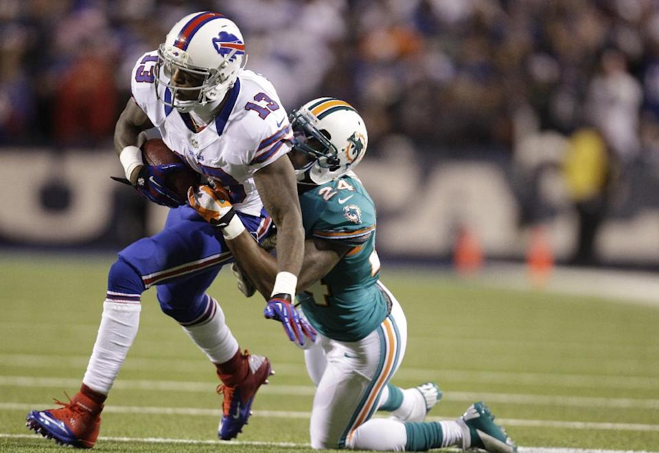 Buffalo Bills wide receiver Steve Johnson (13) is tackled by Miami Dolphins cornerback Sean Smith (24) during the first half of an NFL football game on Thursday, Nov. 15, 2012, in Orchard Park, N.Y. (AP Photo/Gary Wiepert)