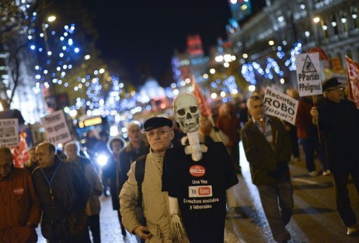 "<p>A demonstrator holds a plastic skeleton with a shirt reading ""Once I had social and labour rights"" during a protest in Madrid on December 17, 2012. Whistles blowing and horns honking, thousands of people demonstrated Monday in Madrid to defend their pensions from the austerity policies of the right-wing government of Mariano Rajoy.</p>"