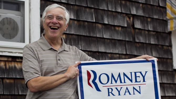 """In this photo taken Oct. 5, 2012, Joe Galli, an independent voter, holds up a sign for the team he'll be voting for in November, in Portsmouth, N.H. New Hampshire's nickname is """"the Granite State"""" but there's nothing solid about its political landscape. Independent voters have been the reason in recent presidential elections. Today, former factory towns to the south _ Manchester and Nashua _ typically vote Republican as do the rural small towns up north, while state capital Concord and university towns like Durham, Dover, Keene and Hanover tend to lean Democratic. And the entire state is peppered with independents like Joe and Thyra Galli of Portsmouth. (AP Photo/Robert F. Bukaty)"""