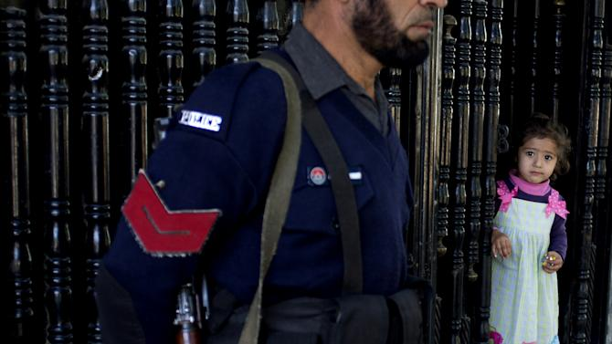 In this Thursday, Oct. 18, 2012 photo, A Pakistani police officer stands guard outside the school of  Pakistani shooting victim Malala Yousufzai, in Mingora, Swat Valley, Pakistan. The Taliban's horrific attack on a female teenage activist in this scenic corner of Pakistan's northwest was the latest in a series of assassination attempts by militant sleeper cells in the area over the last year. The insurgents activated their networks in the Swat Valley to take advantage of the army's decision to reduce its presence, raising questions about the military's ability to hand over control to civilian authorities in areas where it has fought the Taliban, a fundamental part of its counterterror strategy. (AP Photo/B.K. Bangash)