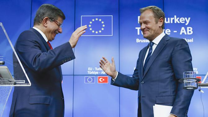 Turkish Prime Minister Ahmet Davutoglu and European Council President Donald Tusk greet each other after a news conference following a EU-Turkey summit in Brussels, Belgium