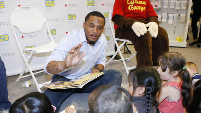 New England Patriots Patrick Chung reads to kids at Macy's Downtown Crossing in Boston as part of the Be Book Smart campaign with Reading Is Fundamental, Tuesday, June 26, 2012. (Bizuayehu Tesfaye /AP Images for Macy's)
