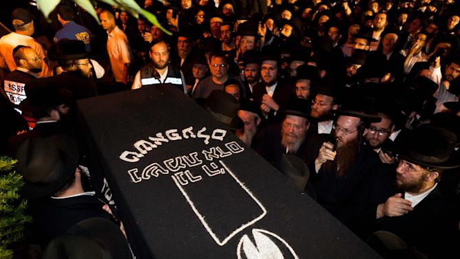 The casket carrying Leiby Kletzky, 8, is carried through a crowd of mourners for a funeral service in the Brooklyn borough of New York Wednesday, July 13, 2011. The boy, who got lost while walking home alone from day camp in his Orthodox Jewish Brooklyn neighborhood, was killed and dismembered by a stranger he had asked for directions, and his remains were found stuffed in a trash bin and the man's refrigerator, police said Wednesday. (AP Photo/John Minchillo)