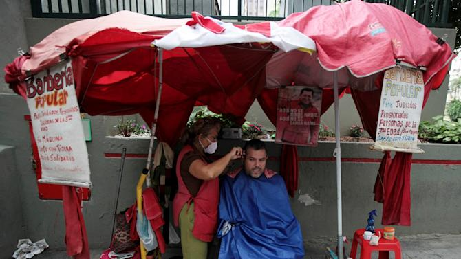 "A man gets his hair cut at a street barbershop decorated with a images of Venezuela's President Hugo Chavez in downtown Caracas,Venezuela, Tuesday, Dec. 11, 2012. Chavez was preparing to undergo a new cancer surgery on Tuesday in Cuba, his government said, after his illness reappeared despite a year and a half of surgeries and treatments. The Venezuelan president announced on Saturday that he needed to undergo a fourth cancer-related surgery after tests showed that ""some malignant cells"" had reappeared in the same area in his pelvic region where tumors were previously removed. (AP Photo/Fernando Llano)"