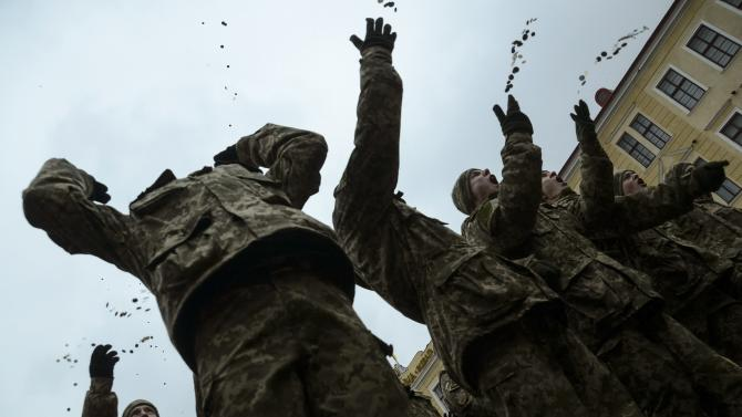 Graduates toss coins in the air at the end of a graduation ceremony at a military academy in Lviv