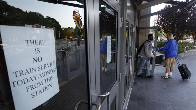 Travelers walk through doors at the Trenton train station early Monday, Aug. 29, 2011, in Trenton, N.J., without seeing a sign that says there is no train service. New Jersey Transit rail service was suspended Monday due to damage from Hurricane Irene. (AP Photo/Mel Evans)