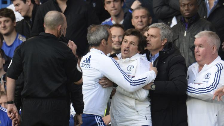 Chelsea's manager Mourinho holds back assistant coach Faria after he was sent off by referee Dean during their English Premier League soccer match against Sunderland in London