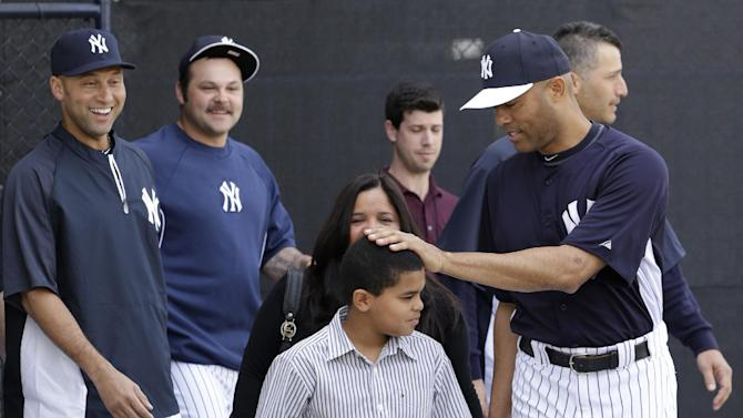 New York Yankees shortstop Derek Jeter, far left,  and reliever Joba Chamberlain, second from left, watch as pitcher Mariano Rivera, far right, pats his son Jaziel on the head before a news conference announcing his plans to retire at the end of the 2013 season at Steinbrenner Field Saturday, March 9, 2013, in Tampa, Fla. Yankees pitcher Andy Pettitte is behind Rivera. Rivera holds baseball's all-time saves leader. (AP Photo/Kathy Willens)