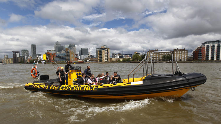 In this Wednesday, July 4, 2012, a high-speed 12-seater rigid inflatable boat, run by the Protection Services International company travels past London's Canary Wharf financial district. Companies like Protection Services International are just one of the many catering to the super rich who are coming to the London games and demand top security and easy transport. (AP Photo/Lefteris Pitarakis)