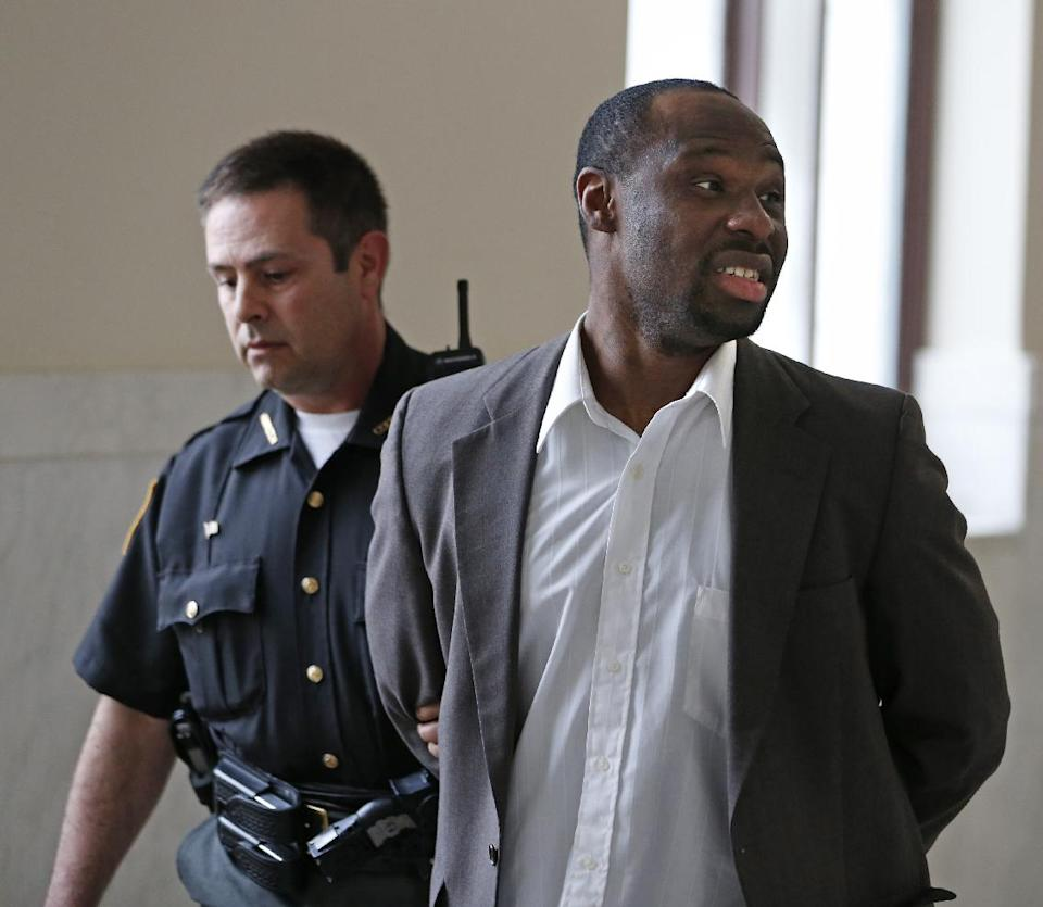 This photo made Thursday, May 16, 2013, in Cincinnati shows Ricardo Woods being taken from court after he was found guilty in the shooting death of a man who authorities say identified his assailant by blinking his eyes while paralyzed. (AP Photo/The Cincinnati Enquirer, Gary Landers)
