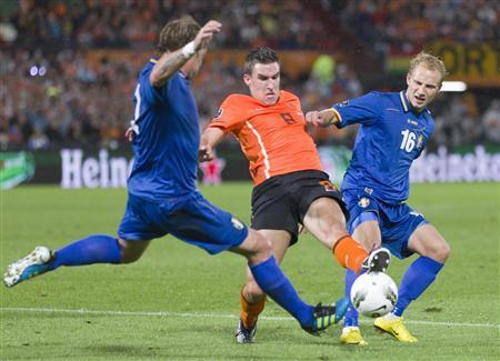 Kevin Strootman of the Netherlands fights for the ball with Igor Armas and Alexandru Suvorov of Moldova during their Euro 2012 soccer qualifier in Rotterdam