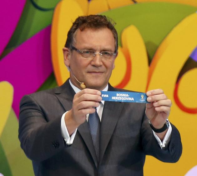 "FIFA Secretary General Jerome Valcke holds the slip showing ""Bosnia & Herzegovina"" during the draw for the 2014 World Cup at the Costa do Sauipe resort in Sao Joao da Mata"
