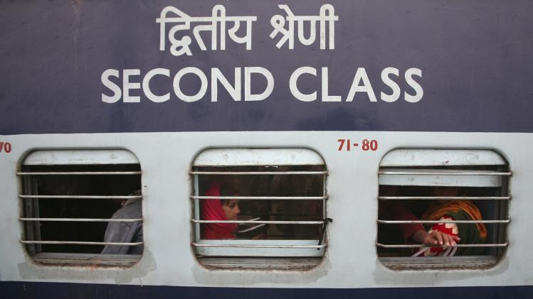 Passengers sit in a train which was delayed due to fog on a cold winter morning at a railway station in Jammu
