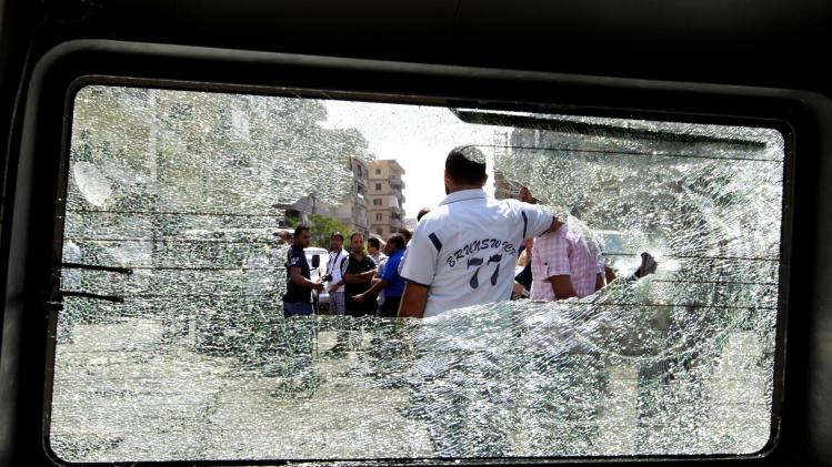 Lebanese civilians are seen through a shattered window of a destroyed car near the Bilal bin Rabbah Mosque where Sunni cleric Sheik Ahmad al-Assir preaches, in the southern port city of Sidon, Lebanon, Tuesday, June 25, 2013. Lebanese security officials say a roadside bomb has exploded on the highway linking Beirut with the Syrian capital without causing casualties. (AP Photo/Bilal Hussein)