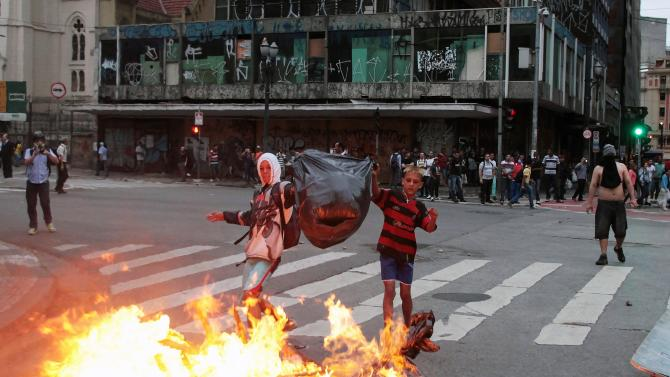 Members of Brazil's Roofless Movement throw garbage on a bonfire during a protest in downtown Sao Paulo