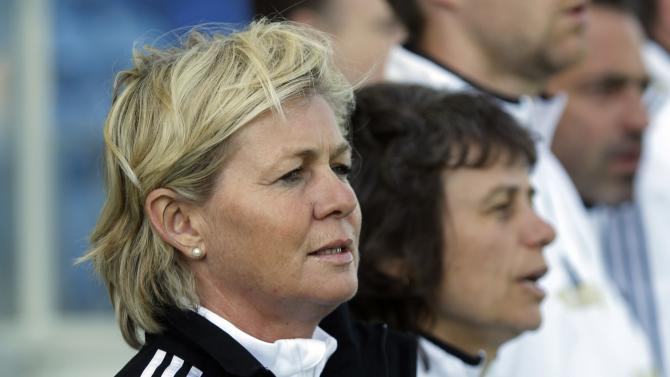 FILE - In this March 12, 2014 file photo Germany's coach Silvia Neid, left, sings the German national anthem prior the women's soccer Algarve Cup final match between Germany and Japan at the Algarve stadium, outside Faro, southern Portugal. German soccer federation DFB announced Monday, March 30, 2015 that Neid will quit as national coach in autumn 2016.  (AP Photo/Francisco Seco)