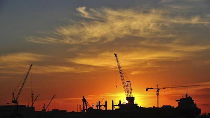 A shipyard is silhouetted against the rising sun in Dalian
