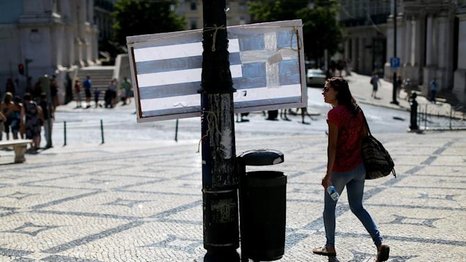 """A woman looks at a board with the Greek flag that reads in Portuguese: """"I love you Greece because the courage against the imperialism!"""", in Lisbon, Monday, July 6, 2015. On Greece's Sunday referendum the majority of voters said """"no"""" to more austerity measures in exchange for another financial bailout. (AP Photo/Francisco Seco)"""