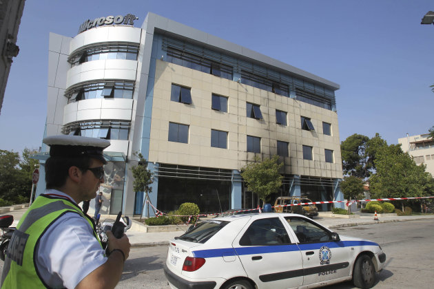 A policeman stands in front of Microsoft's offices in northern Athens, Wednesday, June 27, 2012. Assailants attacked the offices of Microsoft early Wednesday, driving a van through the front doors and