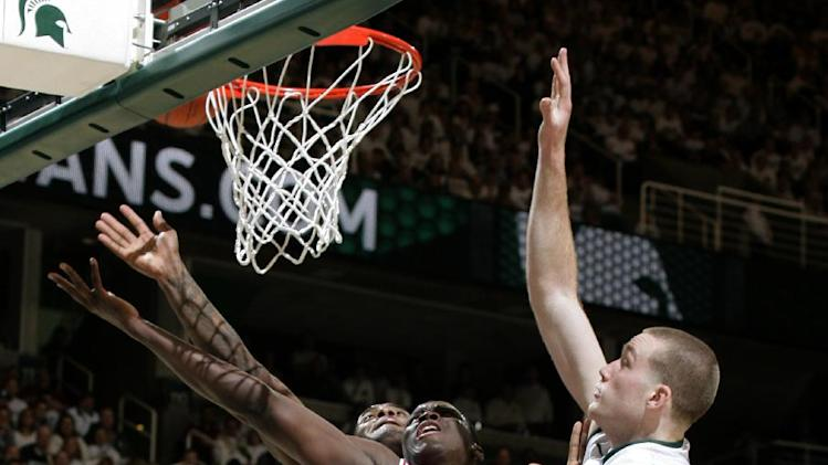 Indiana's Victor Oladipo, center, shoots a layup and draws a foul against Michigan State's Matt Costello, right, and Branden Dawson during the first half of an NCAA college basketball game, Tuesday, Feb. 19, 2013, in East Lansing, Mich. (AP Photo/Al Goldis)