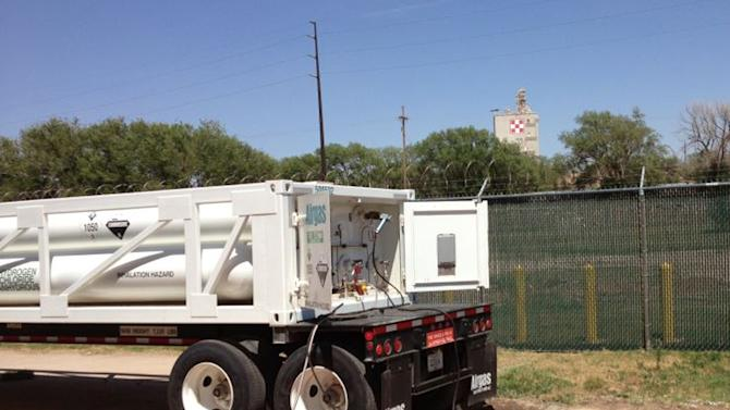 In this photo provided by Bayer CropScience, a trailer with six tanks holding hydrogen chloride is parked at the Bayer CropScience facility near Lubbock, Texas, in early May 2013. Hazardous materials experts were working Thursday to drain the leaking tank into a recovery tank. The leak forced the evacuation of about 100 families beginning Wednesday, May 8, 2013. The mandatory and voluntary evacuation was lifted late Thursday. An official said it will take up to two days to drain the tank. (AP Photo/Bayer CropScience, Monty Christian) NO SALES