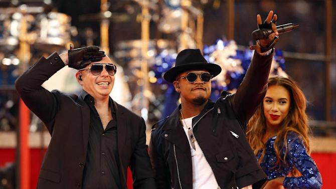 Rappers Pitbull, left, and Ne-Yo salute fans after performing at halftime at an NFL football game between the Philadelphia Eagles and the Dallas Cowboys, Thursday, Nov. 27, 2014, in Arlington, Texas. (AP Photo/John F. Rhodes)