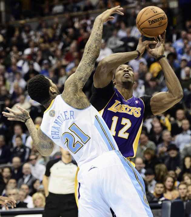 Los Angeles Lakers' Howard looses control of ball under pressure from Denver Nuggets' Chandler during NBA basketball game in Denver