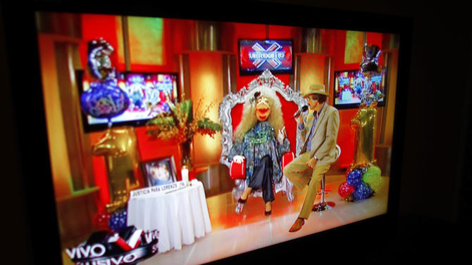 "In this Oct. 17, 2012, a TV show called ""La Comay"" (roughly translated to ""The Godmother""), is seen on a TV set in San Juan, Puerto Rico. This five-foot tall puppet with outlandish red lips, a shrill voice and a penchant for salacious details rules Puerto Rico's gossip circuit, with legions tuning into her show every afternoon ready for the latest bombshell. And La Comay dishes it out with ominous music playing in the background, talking about everyone from Mexican crooner Luis Miguel to Puerto Rico's own Miss Universe beauty queen Zuleyka Rivera. (AP Photo/Ricardo Arduengo)"
