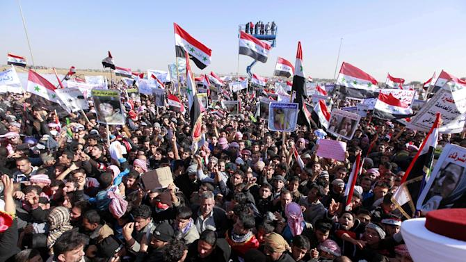 Protesters chant slogans against Iraq's Shiite-led government as they wave national flags during a demonstration in Ramadi, 70 miles (115 kilometers) west of Baghdad, Iraq, Wednesday, Dec. 26, 2012. Thousands of Iraqi demonstrators massed in a Sunni-dominated province west of Baghdad Wednesday, determined to keep up the pressure on a Shiite-led government that many accuse of trying to marginalize them. (AP Photo/ Hadi Mizban)