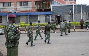 Kenya security personnel walk to their positions outside…