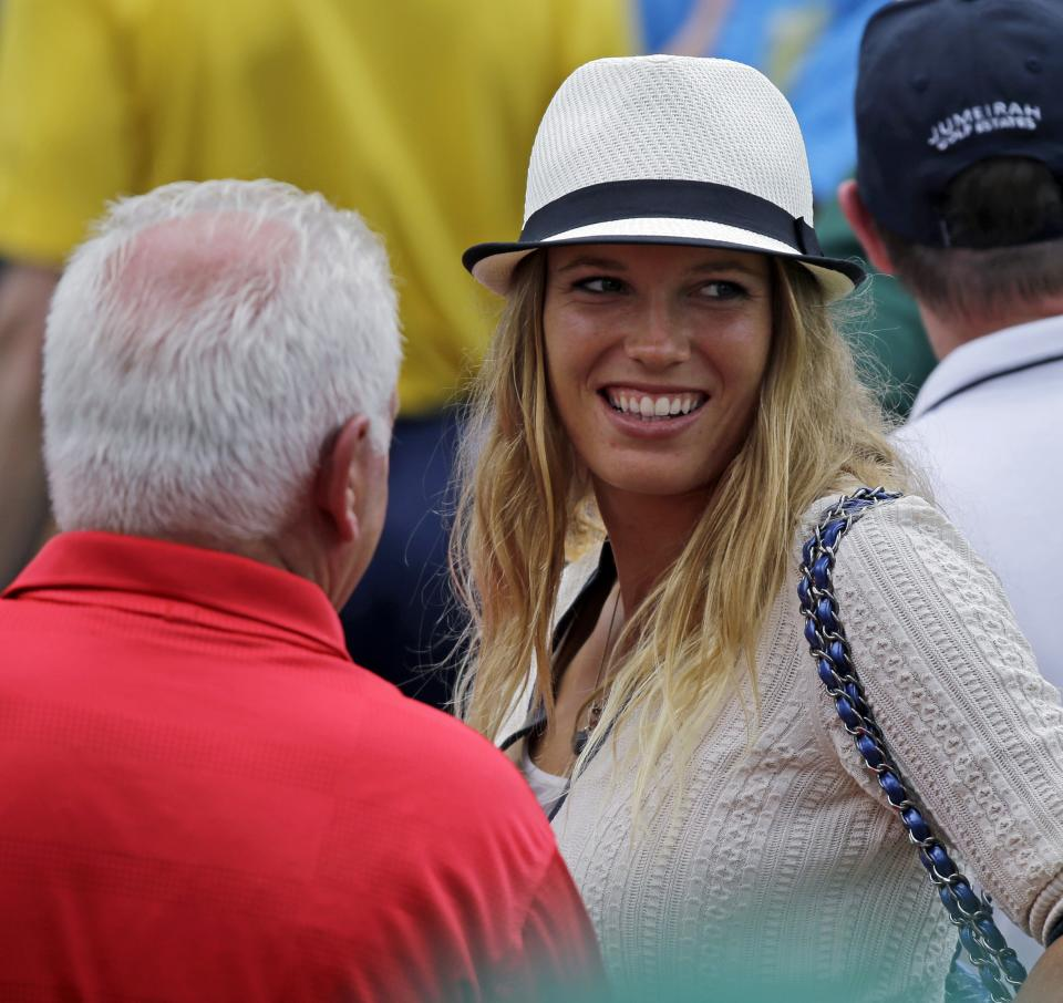 Tennis player Caroline Wozniacki speaks with Northern Ireland's Rory McIlroy's father Gerry McIlrory during the first round of the Masters golf tournament Thursday, April 11, 2013, in Augusta, Ga. (AP Photo/David J. Phillip)