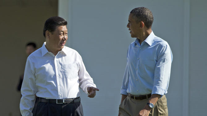 President Barack Obama, right, walks with Chinese President Xi Jinping at the Annenberg Retreat at Sunnylands on Saturday, June 8, 2013, in Rancho Mirage, Calif. Obama and Xi are wrapping up a two-day summit at which they tackled the contentious issue of cybersecurity and tried to forge closer ties between the leaders of the world's largest economies. (AP Photo/Evan Vucci)