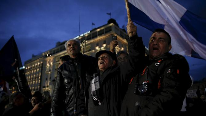Farmers shout slogans and wave Greek national flags on the back of a pickup truck during a protest against planned pension reforms in front of the parliament building in Athens
