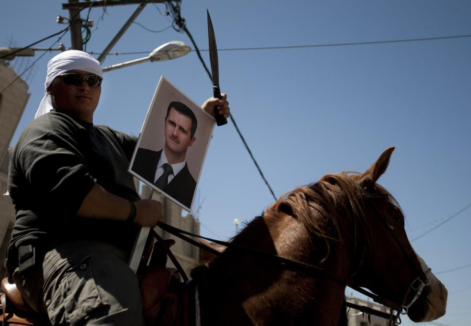 Druze man rides a horse while holding a knife and a photograph of Syrian President Bashar Assad during Syria's Independence Day in the village of Majdal Shams in the Golan Heights, near the border with Syria and Israel, Tuesday, April 17, 2012. (AP Photo/Ariel Schalit)