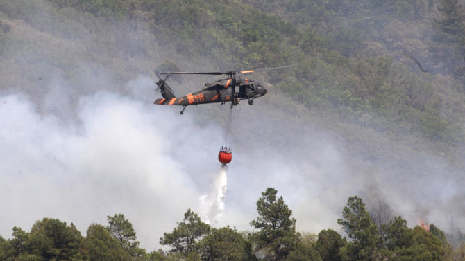 A helicopter dumps water on smoke billowing from a forest fire north of Raton, N.M., Wednesday, June 15, 2011. Crews raced to get a jump on flames marching along the New Mexico-Colorado border and through the rugged desert canyons on the opposite on end of the state Wednesday before the weather took a turn for the worse.  (AP Photo/Rick Bowmer)