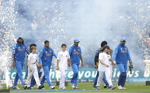 India's captain MS Dhoni , right, leads his players accompanied by children mascots onto the pitch, as fireworks explode for the start of the ICC Champions Trophy semifinal between India and Sri Lanka