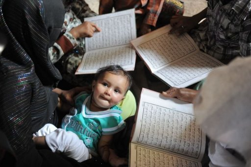 A child looks on as survivors of the 2002 Gujarat communal riots gather and read the Koran at the Gulberg Society in Ahmedabad to mark the tenth anniversary. An Indian court Monday sentenced 21 people to life imprisonment over the massacre of 11 Muslims during some of the country's worst religious riots a decade ago in Gujarat