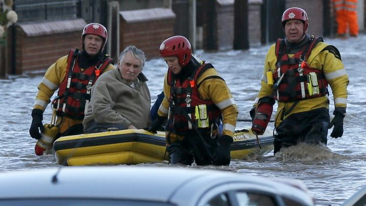 Emergency rescue service workers evacuate a resident in an inflatable boat in flood water in a residential street in Rhyl