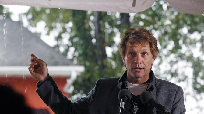 "Rock star Jon Bon Jovi gestures as he answers a question outside the Soul Kitchen restaurant in Red Bank, N.J., Wednesday, Oct. 19, 2011, during the opening of the ""pay-what-you-can"" charity restaurant. Diners pay whatever they're able to. Those without money can still eat provided they're willing to work in the restaurant or perform some community service. (AP Photo/Mel Evans)"