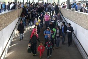 Migrants walk on the platform after arriving by train…