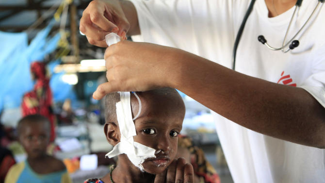 """Suldano Osman, 1, is steadied by her mother's hand as a pediatrician attaches a feeding tube to aid her treatment for malnutrition, at a Doctors Without Borders hospital in Dagahaley Camp, outside Dadaab, Kenya, Monday, July 11, 2011. U.N. refugee chief Antonio Guterres said Sunday that drought-ridden Somalia is the """"worst humanitarian disaster"""" in the world, after meeting with refugees who endured unspeakable hardship to reach the world's largest refugee camp in Dadaab, Kenya. (AP Photo/Rebecca Blackwell)"""