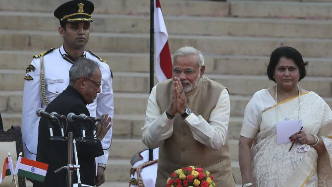 India's new prime minister Narendra Modi, center, greets President Pranab Mukherjee, left, after taking oath of office at the presidential palace in New Delhi, India, Monday, May 26, 2014. Modi's inauguration is the first to which India invited leaders from across South Asia. (AP Photo /Manish Swarup)