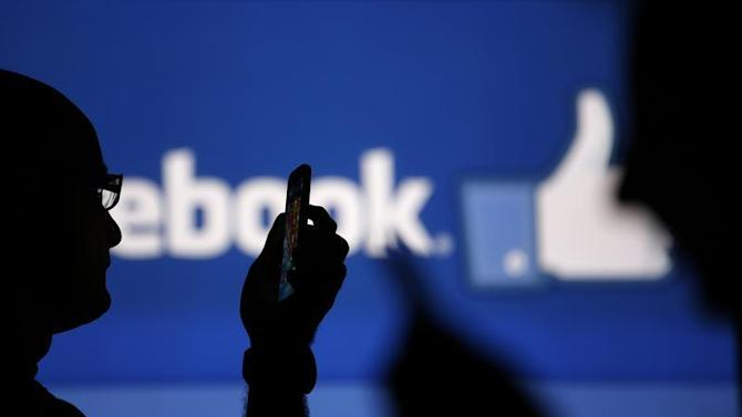 Men are silhouetted against a video screen with an Facebook logo as he poses with an Nokia Lumia 820 and Samsung Galaxy S4 in this photo illustration taken in the central Bosnian town of Zenica