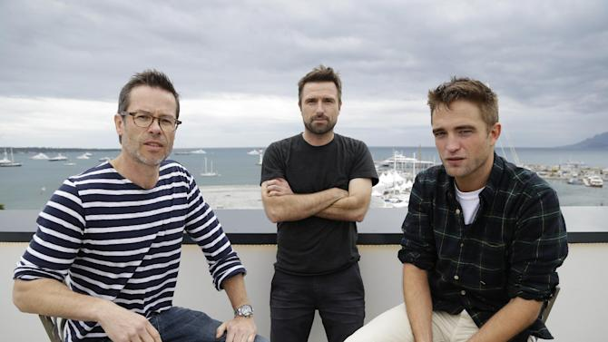 "FILE - In this May 19, 2014 file photo, from left, actor Guy Pearce, director David Michod and actor Robert Pattinson pose for a portrait to promote ""The Rover,"" at the 67th international film festival, Cannes, southern France. Four years after his breakthrough debut feature film ""Animal Kingdom,"" the Australian director Michod has finally followed up his surprise, Oscar-nominated sensation with a lean dystopian thriller starring Guy Pearce and Robert Pattinson. ""There was a level of anxiety there because I did after a while start to go, 'I don't know what my second move is,'"" says Michod. (AP Photo/Thibault Camus, file)"