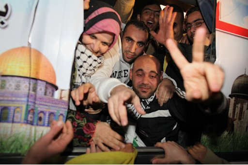 Freed Palestinian prisoners gesture upon arrival at Rafah crossing in the Gaza Strip