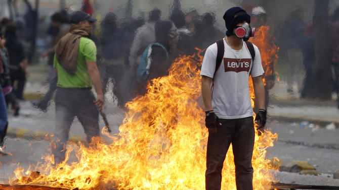 A demonstrator stands next to a burning barricade on the second day of a national strike in Santiago, Chile, Thursday Aug. 25, 2011. Chileans marched Thursday, demanding profound changes in the country's heavily centralized and privatized form of government. Union members, students, government workers and Chile's center-left opposition parties joined the nationwide two-day strike.  (AP Photo/Roberto Candia)