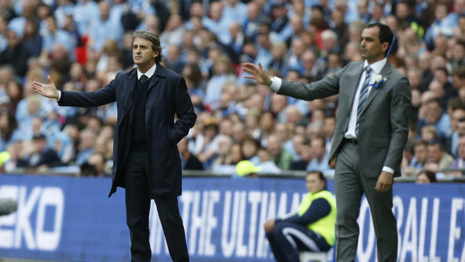 Manchester City's manager Roberto Mancini, left, and Wigan Athletic's manager Roberto Martinez react as they watch their teams play during their English FA Cup final soccer match at Wembley Stadium, London, Saturday, May 11, 2013. (AP Photo/Matt Dunham)