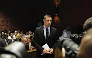 Oscar Pistorius stands in the dock during a break in court proceedings at the Pretoria Magistrates court, February 20, 2013. &quot;Blade Runner&quot; Pistorius, a double amputee who became one of the biggest names in world athletics, was applying for bail after being charged in court with shooting dead his girlfriend, 30-year-old model Reeva Steenkamp, in his Pretoria house. REUTERS/Siphiwe Sibeko