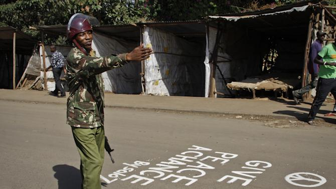 A police officer from the General Service Unit gestures to a crowd of people gathered to go home, as he stands next to a peace slogan painted on the road by a graffiti artist, in the Kibera slum of Nairobi, Kenya Saturday, March 9, 2013. Uhuru Kenyatta - the son of Kenya's founding father and a man accused by an international court of helping orchestrate the vicious violence that marred the nation's last vote - was certified as the winner on Saturday of Kenya's presidential election by the slimmest majority - 50.07 percent. (AP Photo/Khalil Senosi)